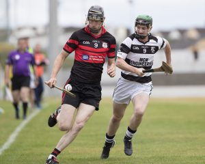 David Phelan of Mount Leinster Rangers goes on a solo run as Mark McDonald of Erin's Own gives chase during the group stage clash between the two sides in August Photo: Thomas Nolan Photography