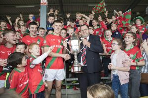 Palatine captain Jason Kane is presented with the Conlon Cup by Carlow GAA chairman Sean Campion