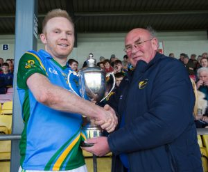 Liam Barry (Leinster council delegate) presents the cup to St Andrew's captain John Doyle