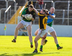 St Andrew's goalkeeper Rory Doyle claims the ball ahead of Naomh Eoin's Kevin Foley as Morgan Drea closes in